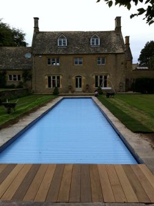 Outdoor skimmer swimming pool with slatted cover closed