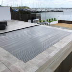 Thermal slatted pool cover closed on an infinity pool